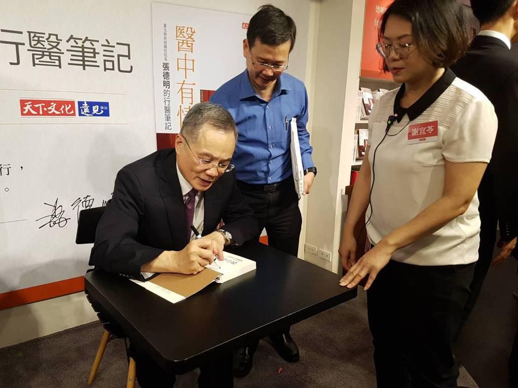 張德明為讀者簽書。記者楊雅棠/攝影