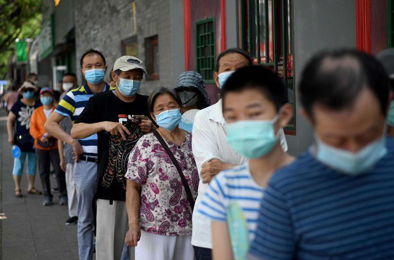 北京20日新增22個新冠肺炎確診病例,10天以來已累計227例,市民排隊接受核酸檢測。 (法新社)