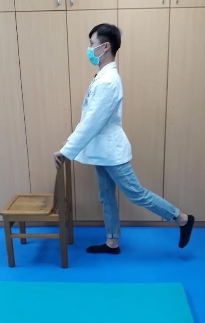 負重運動之臀大肌肌力訓練,手扶椅子,膝蓋保持伸直,大腿向後抬起。 圖/衛福部苗栗...
