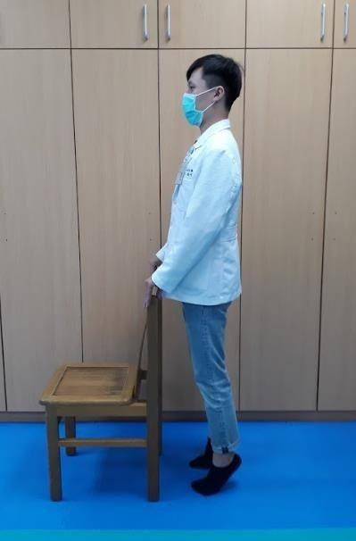 負重運動之腓腸肌肌力訓練,手扶椅子,膝蓋保持伸直,墊起腳尖。 圖/衛福部苗栗醫院...