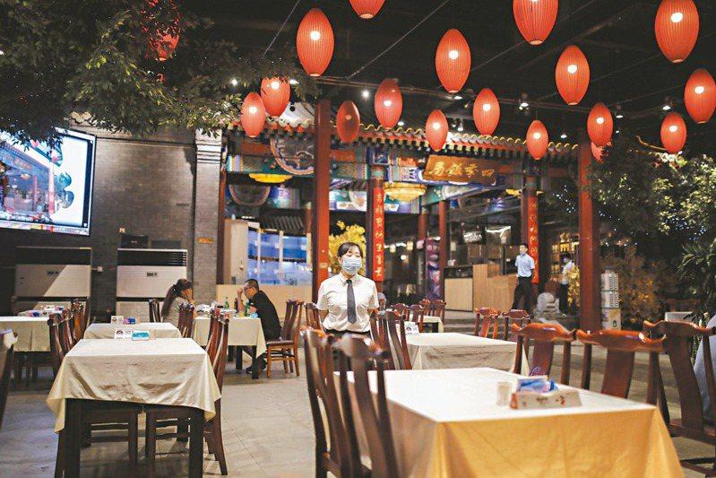 北京疫情突然升溫後,原本逐漸復甦的北京餐飲業,再次遭受重擊,餐廳裡服務員比顧客多。 (歐新社)