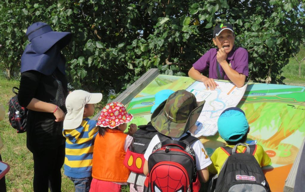 溼地導覽員向大小朋友細說板橋河岸溼地故事。 信義房屋/提供