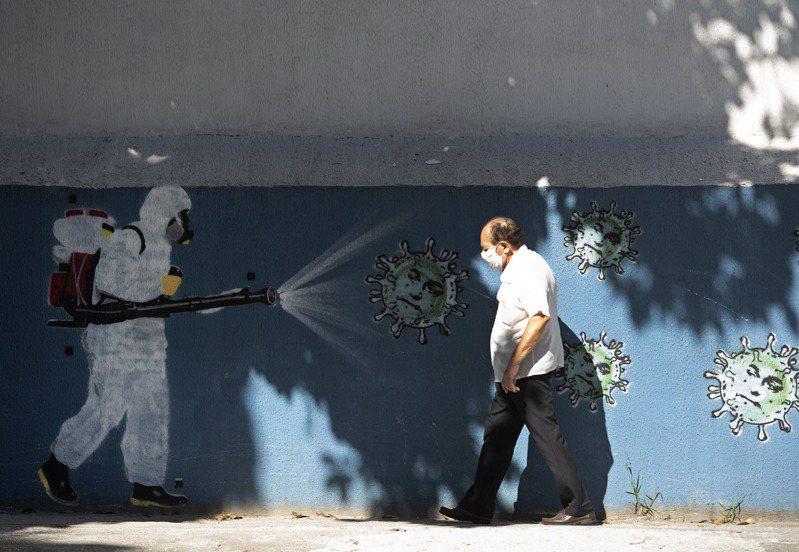 全球各地在過去24小時創下疫情爆發以來單日最高確診紀錄,巴西居第一。圖為里約熱內盧市一工人身著防護服在街頭消毒。(美聯社)