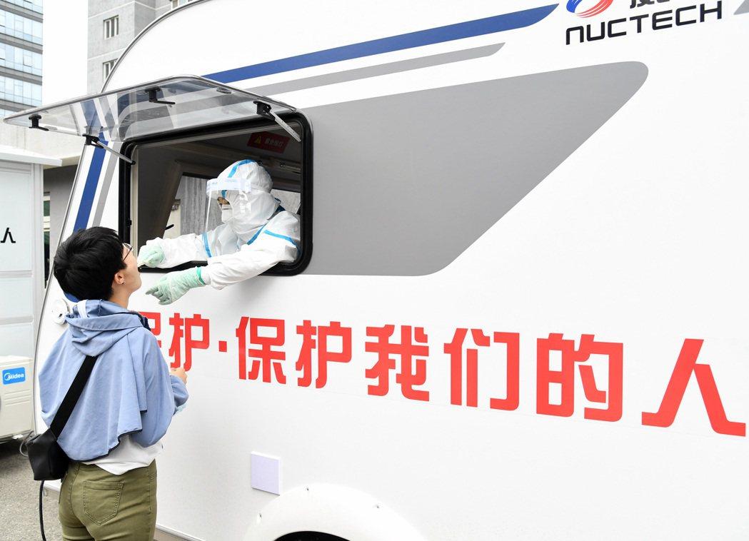 圖為北京安貞醫院醫護人員24日在防疫檢測移動艙內為民眾進行咽拭子採集。(新華社)