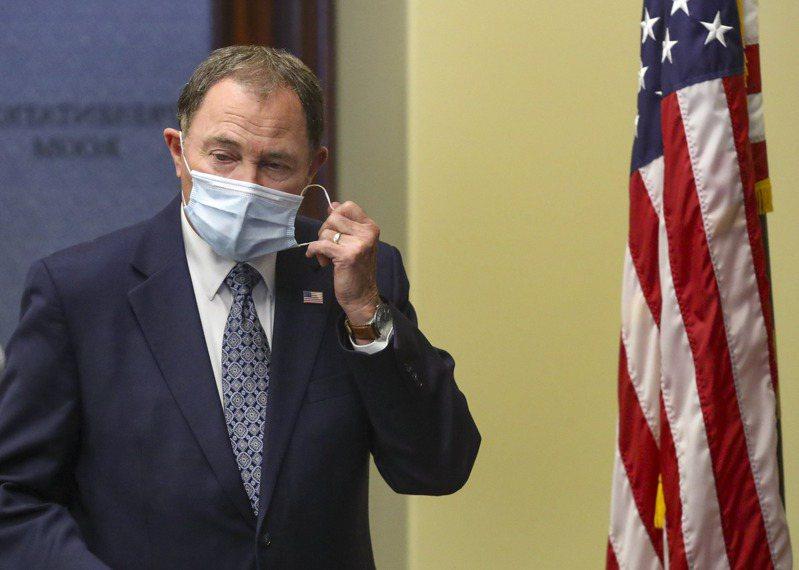 圖為美國猶他州州長蓋里‧赫伯特(Gary Herbert)在每日例行疫情簡報演說前脫下口罩情形。美聯社