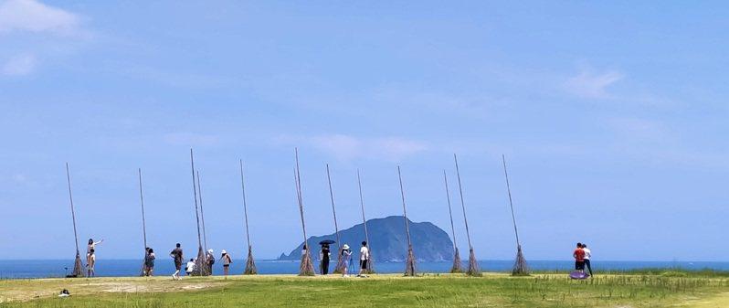 端午連假首日,基隆市知名景點潮境公園25日有不少民眾頂著豔陽前來,與飛天掃帚裝置藝術拍照留念。 中央社