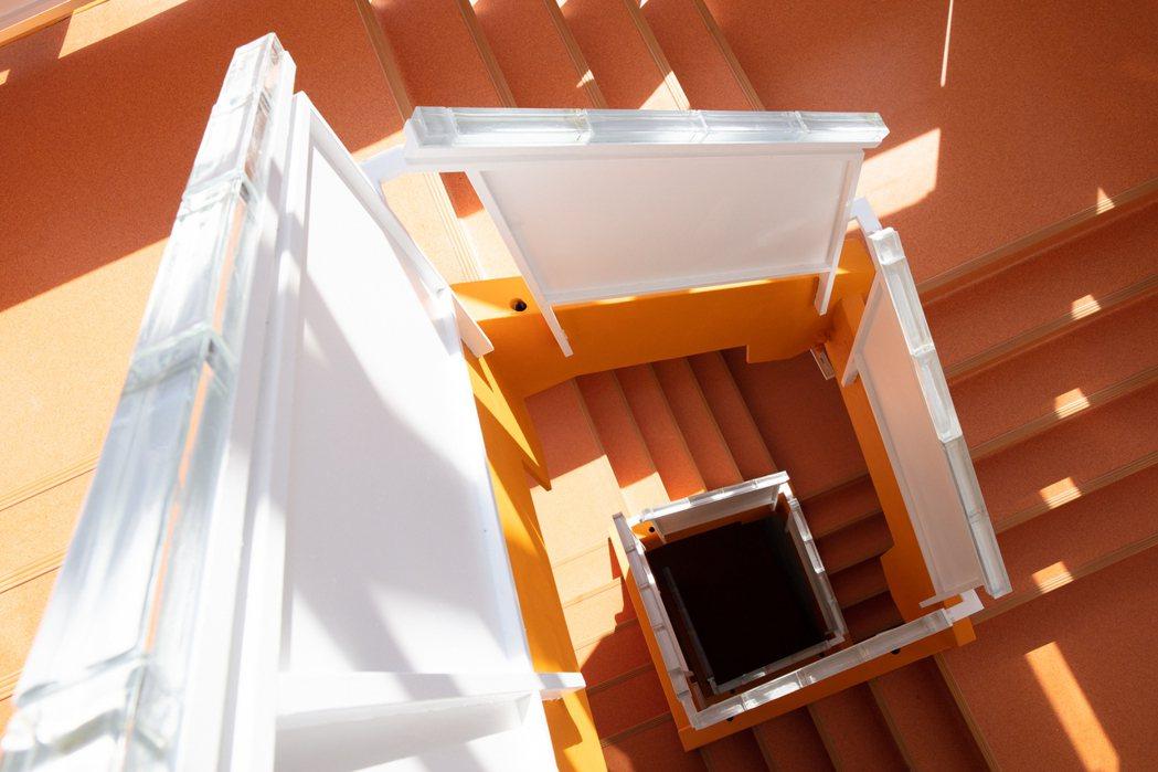 流動感強烈的橘色迴轉樓梯形成獨特的「梯間美術館」。 圖/丰宇影像