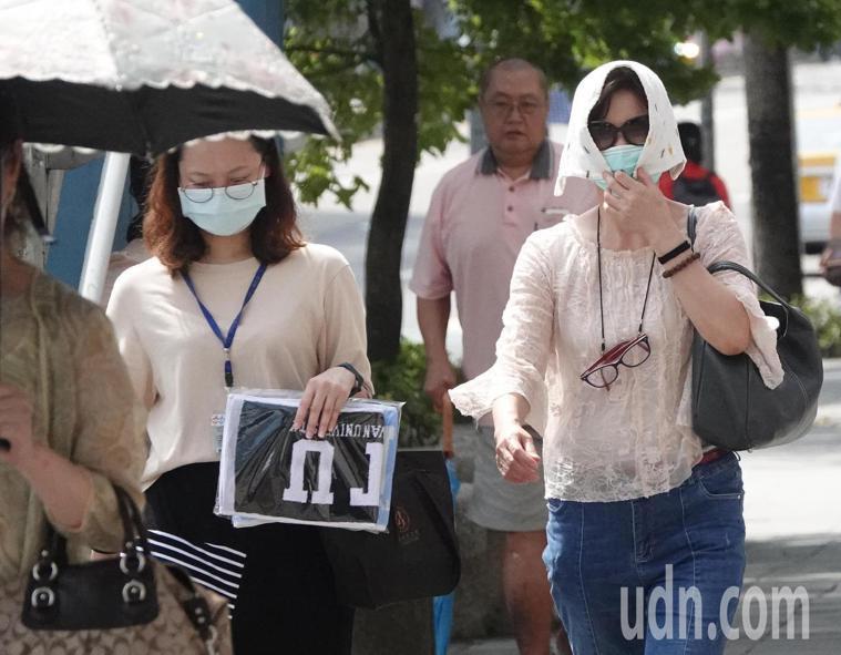台北街頭飆高溫,有民眾用毛巾蓋頭防曬。報系資料照片
