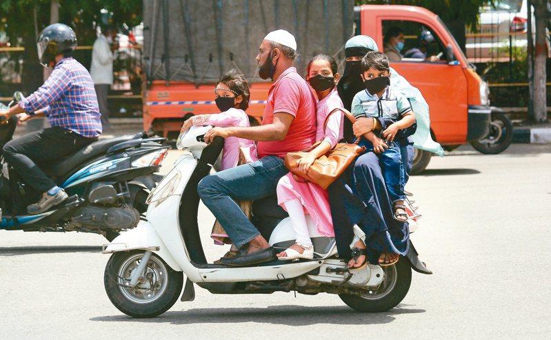 新冠肺炎疫情癱瘓全球經濟,損害可能持續十年,圖為印度一個家庭戴口罩騎車畫面。 (歐新社)