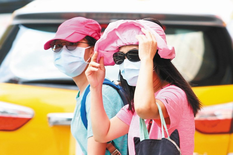 台北廿三日飆出攝氏38.4度高溫,醫師提醒民眾外出要撐傘、戴帽,並注意補充水分。 記者蘇健忠/攝影