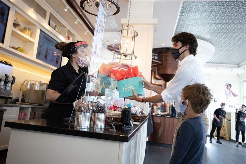 24日是魁北克省省慶日,加拿大總理杜魯多(白衣者)和兒子哈德瑞恩(前)戴著口罩,現身加蒂諾的巧克力專賣店。(取材自臉書)  張詒宣