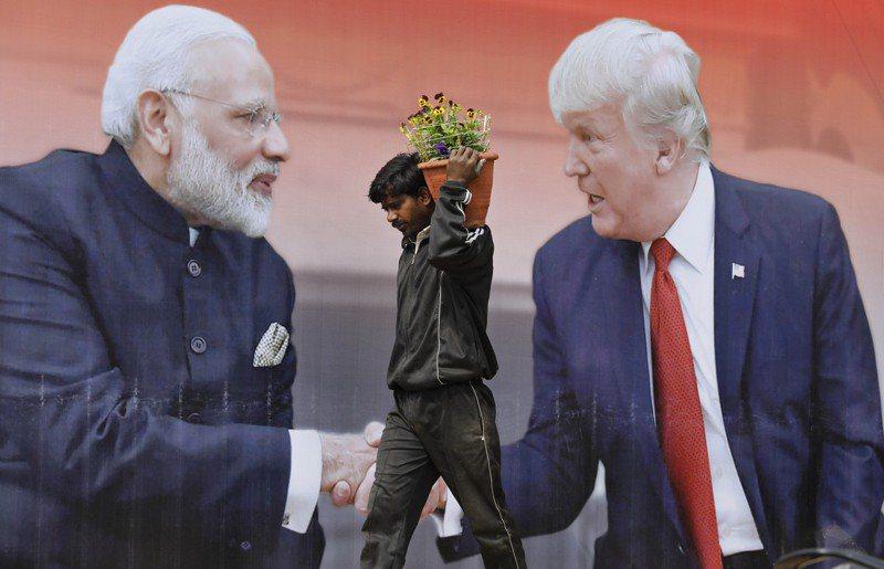 美國總統川普22日決定暫停簽發H-1B、H-2B等工作簽證,衝擊聘雇許多印度裔高科技人才的美國科技業。圖為一名印度勞工行經阿格拉市一個川普與印度總理莫迪握手的大型看板。 美聯社