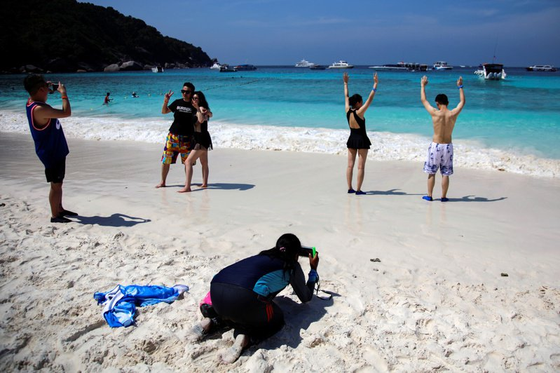 中國大陸觀光客在泰國攀牙(Phang-Nga)一島嶼海灘上拍照遊玩。  路透