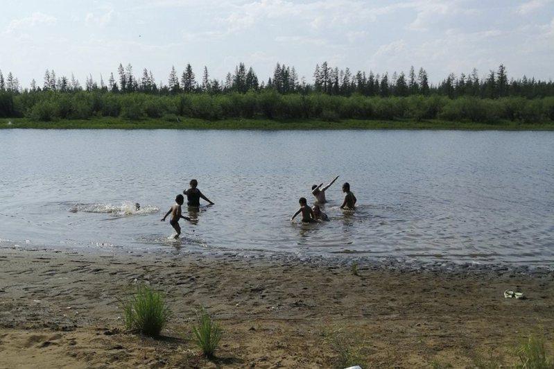 西伯利亞北極圈小鎮維科揚斯克今年氣溫異常溫暖,孩童21日在當地一座湖泊戲水。美聯社
