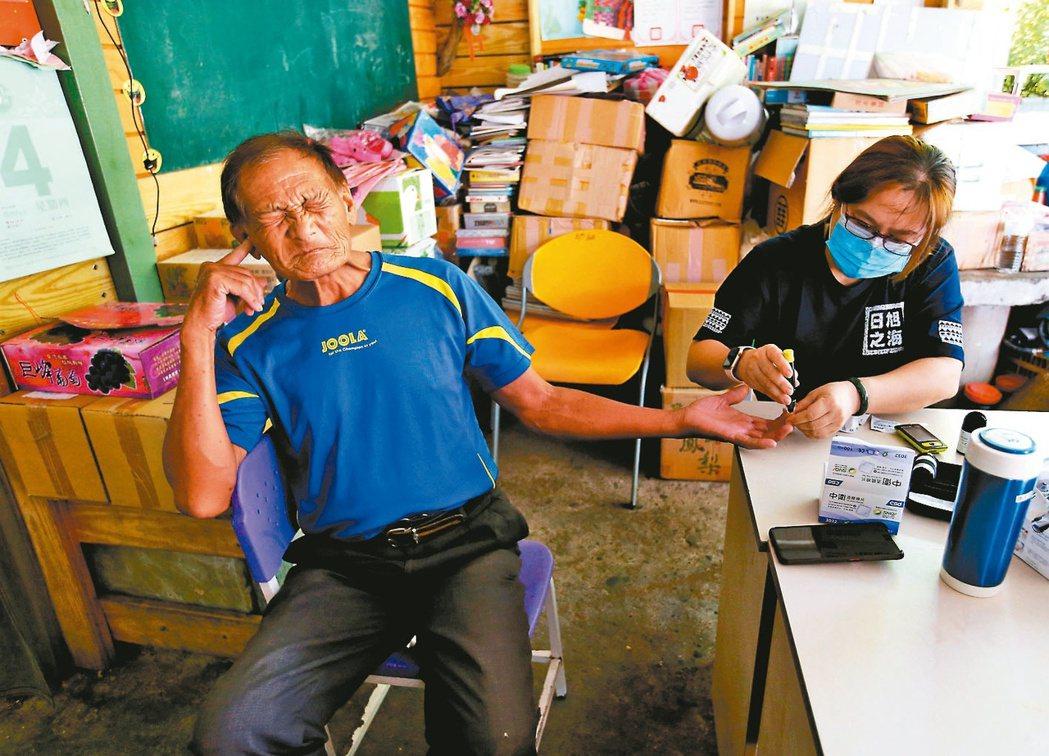 旭海小學堂創辦人潘儀芳(右)幫社區長者量血壓、血糖。記者林澔一/攝影