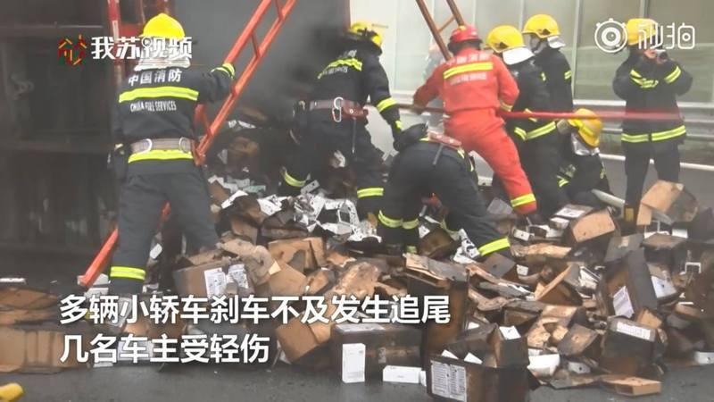 消防員為撲滅火種,不停翻動貨物。(影片截圖)