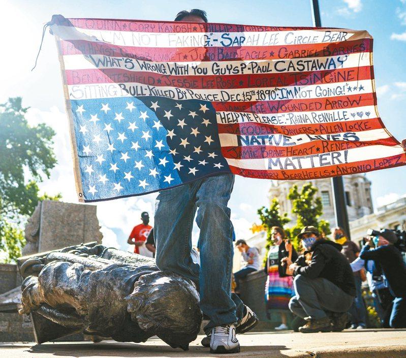 美國明尼蘇達州聖保羅市的哥倫布雕像日前被推倒,一名原住民用膝蓋壓住雕像的頸部。 美聯社