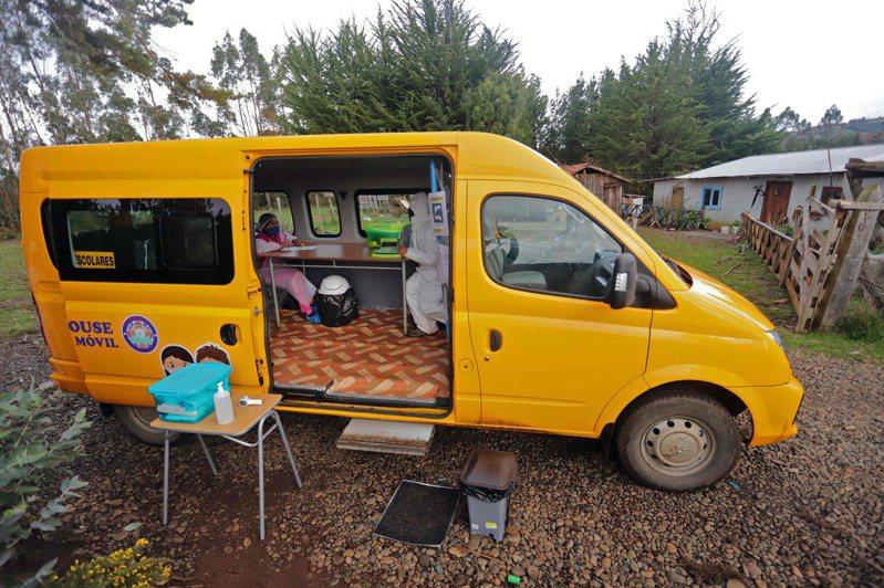 由於新冠肺炎疫情封鎖期間,許多智利學童無法上網參加線上課程,因此夢之屋學校派遣老師和廂型車,把車子停在學童家門口授課。(法新社)