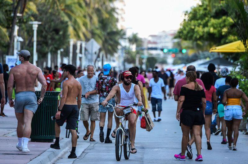 美國佛羅里達州26日新增確診案例創單日新高,近1000人,當局已下令升高部分防疫措施。圖為佛州邁阿密灘26日的人潮。 法新社