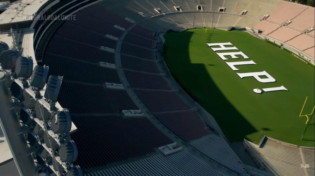 麥莉在空無一人的足球場演唱,地面上並擺置著「HELP(幫忙)」的字樣。圖/摘自Y...