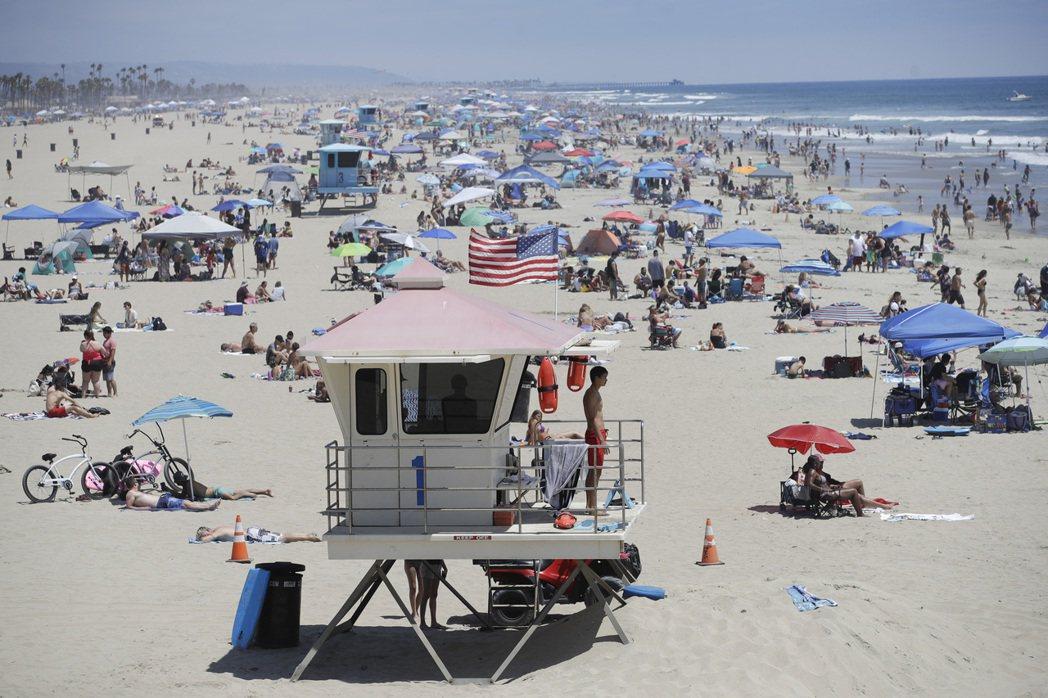 美國加州杭亭頓海灘市的沙灘27日滿是遊客,一名救生員站在高處監看。(美聯社)