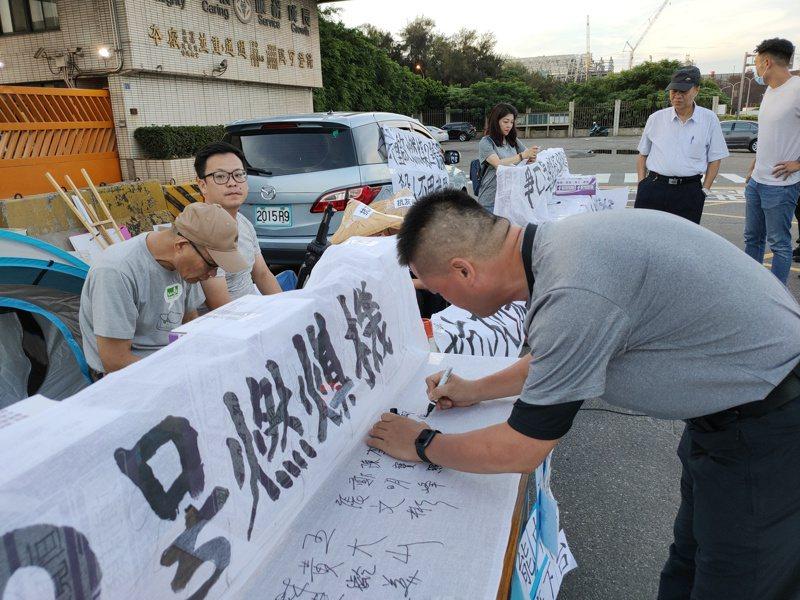 台中市议员罗廷玮和黄健豪在台中火力发电厂前静坐抗议,声援者到场签名。 记者黄寅/摄影