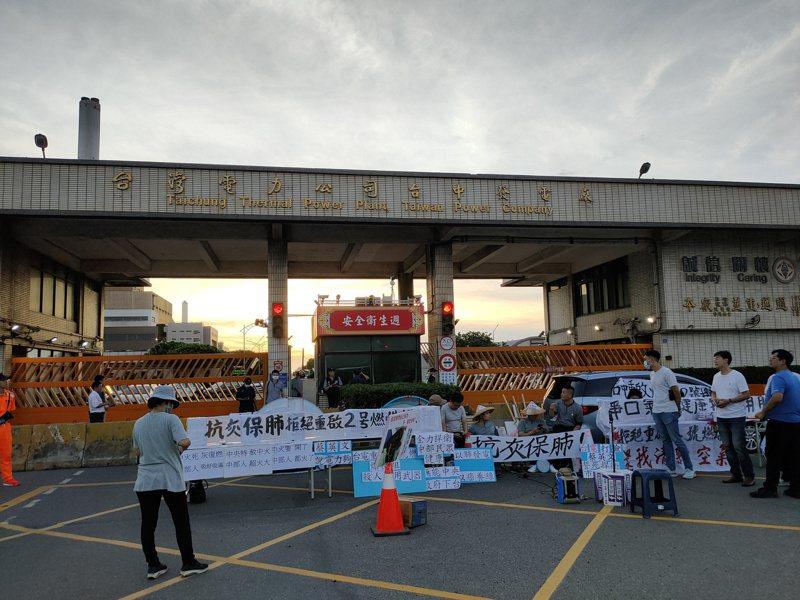 台中市议员罗廷玮和黄健豪在台中火力发电厂前静坐抗议。 记者黄寅/摄影