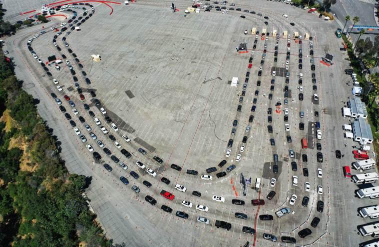 美國新冠疫情惡化,圖為洛杉磯道奇體育館外,等著做病毒檢測的車輛。(法新社)