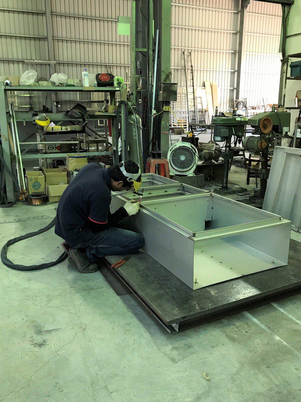 焊接機電箱體的現場操作人員。宋依靜/攝影。