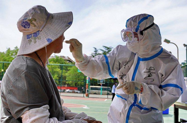 大陸昨新增確診12例,其中本土7例都在北京。圖為北京疫情最嚴重的豐台區採樣點,工作人員為市民做咽拭子採樣。(新華社)