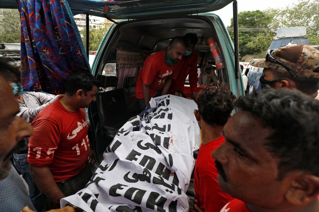 巴基斯坦消防員29日在喀拉蚩巴國證交所外,將一名槍手的遺體搬離現場。(路透)