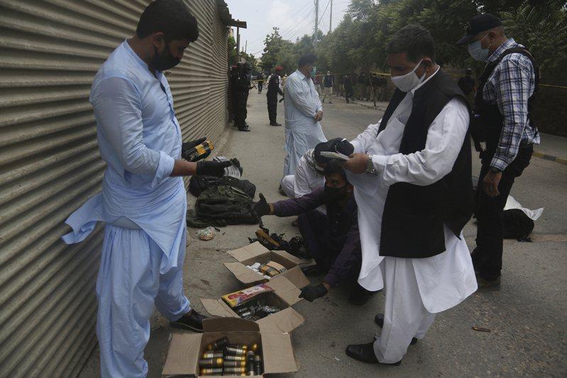 巴基斯坦安全人員29日在喀拉蚩證交所外檢查槍手的彈藥。(美聯社)