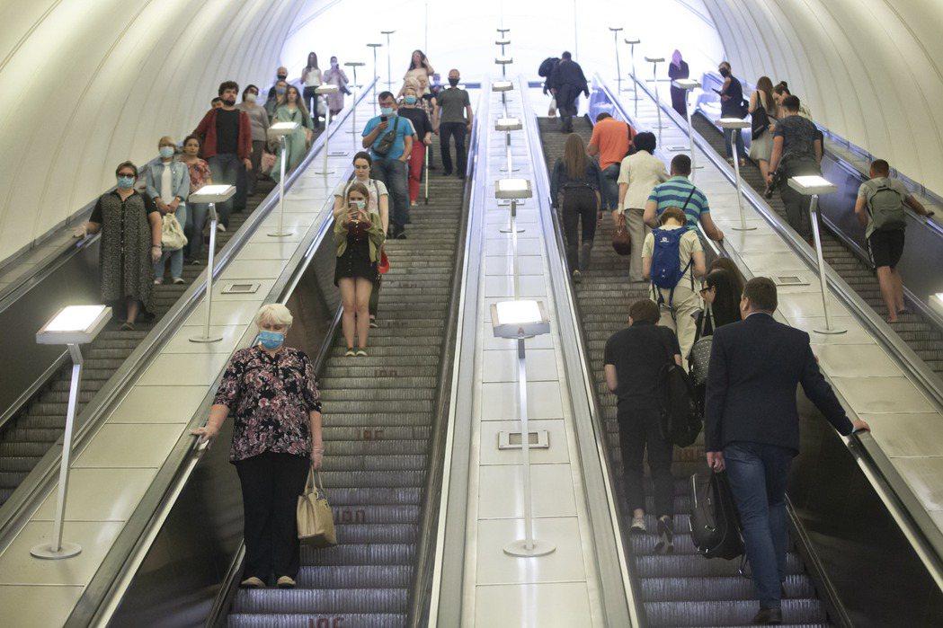俄國疫情逐漸趨緩,圖為23日莫斯科一處地鐵站內民眾人口一罩搭乘電扶梯畫面。新華社