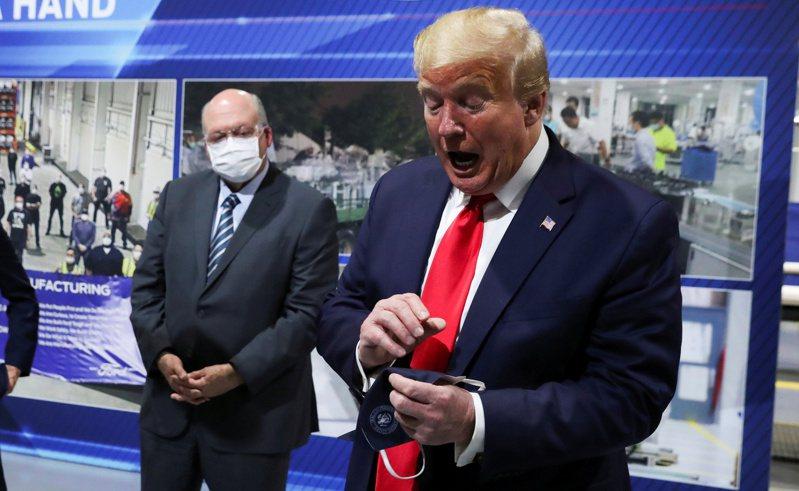 美國總統川普5月21日在視察密西根州伊斯蘭提市的福特汽車公司零件廠時,拿著一個據他說他先前戴過的口罩。路透