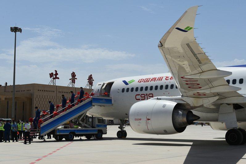 大陸國產C919客機飛抵吐魯番,開展高溫專項試飛。圖為6月28日,C919客機降落在吐魯番交河機場,工作人員走下飛機。(新華社)