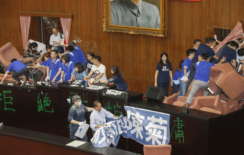 國民黨團前天突襲佔據立法院議場,民進黨立委昨天展開反攻,衝進場將國民黨的標語撕下。記者鄭超文/攝影
