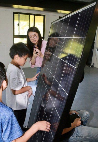 陽光伏特家營運管理洪寧均向課輔班學生介紹太陽能板運作原理。記者黃義書/攝影