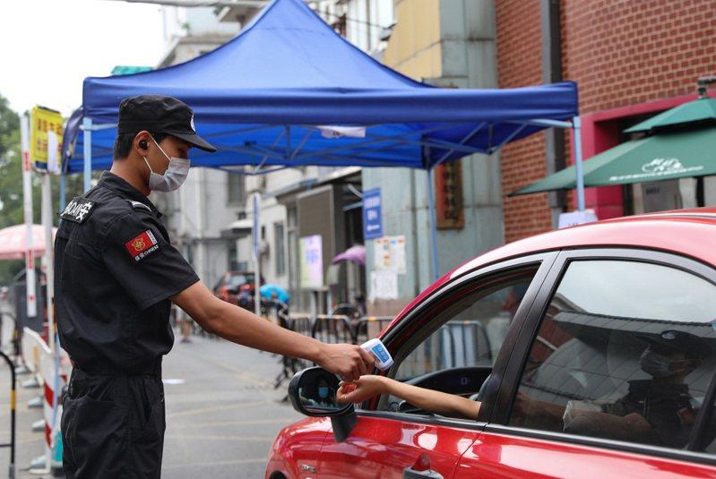 圖為北京市海淀區一處小區,保安正在為入小區的居民測量體溫。(中新社)