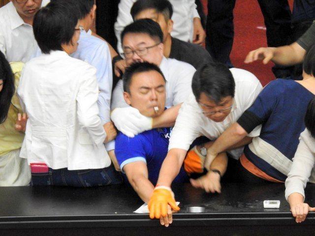 民進黨立委以優勢人力清場,綠委吳秉叡(中後)在藍綠推擠衝突中以手肘勒住藍委洪孟楷脖子。圖/洪孟楷辦公室提供
