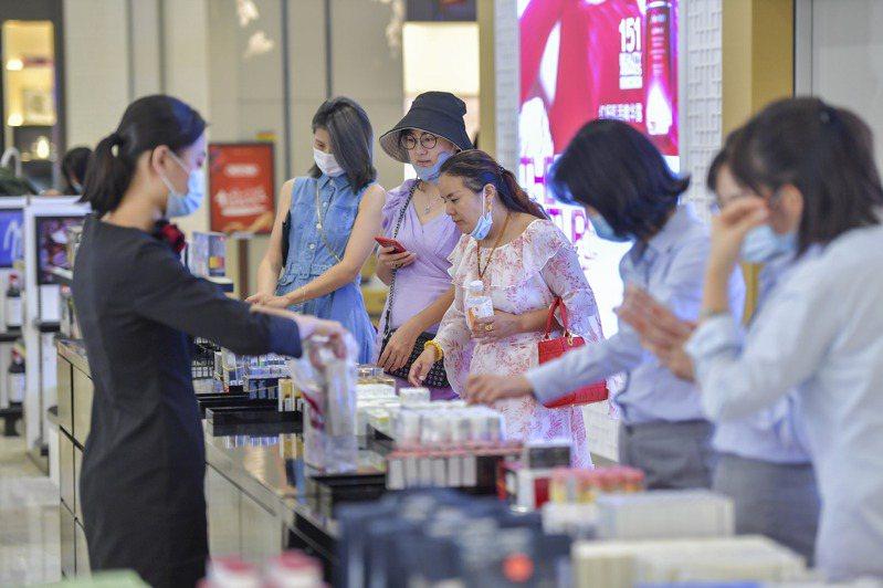 海南免稅購物額度從每年每人3萬元提高至10萬元,圖為遊客在海口日月廣場免稅店選購免稅商品。(中新社)
