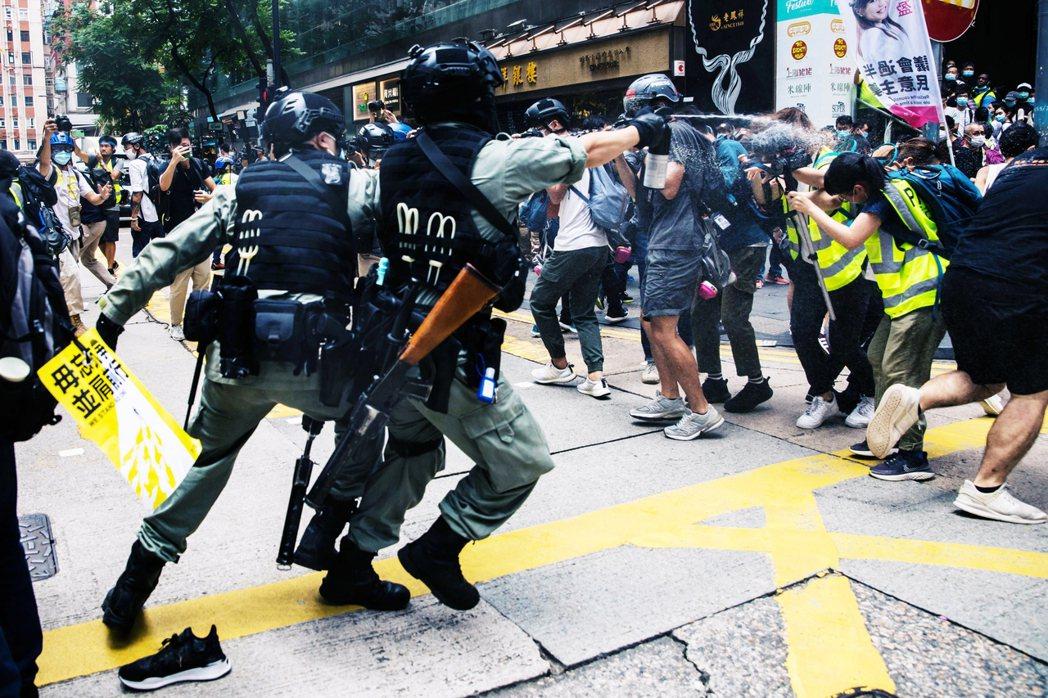 鎮暴警察向記者與群眾噴灑胡椒水。 圖/法新社