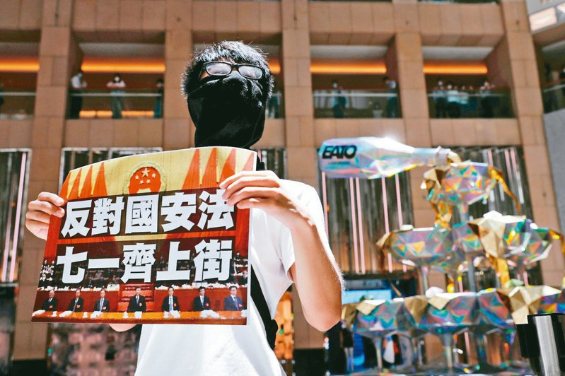 北京通過港版國安法後,香港示威者手持「七一齊上街」的看板進行動員。(路透)