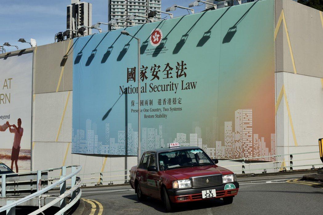 6月30日,香港多棟建築物上展示支持國安立法的巨幅公益廣告,巨幅廣告上用中英文書...