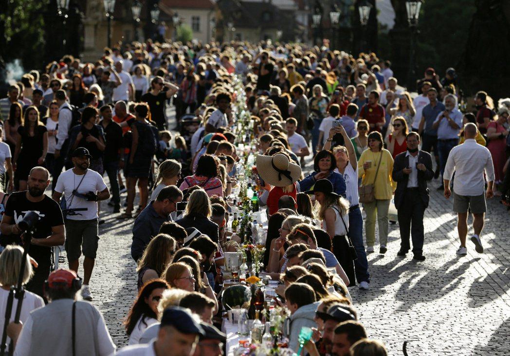 布拉格民眾在查理士橋上互相分享帶來的美食、飲料。路透