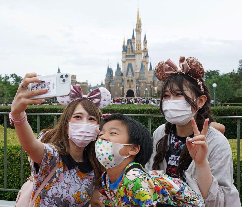民眾一日在東京迪士尼樂園自拍。東京迪士尼因新冠病毒疫情關閉四個月,一日恢復營業。(法新社)