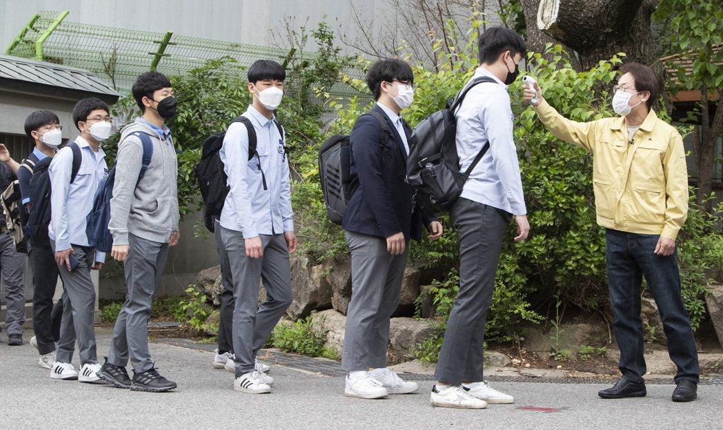 韓國首爾景福高等學校的學生在入校前接受體溫檢測。 新華社