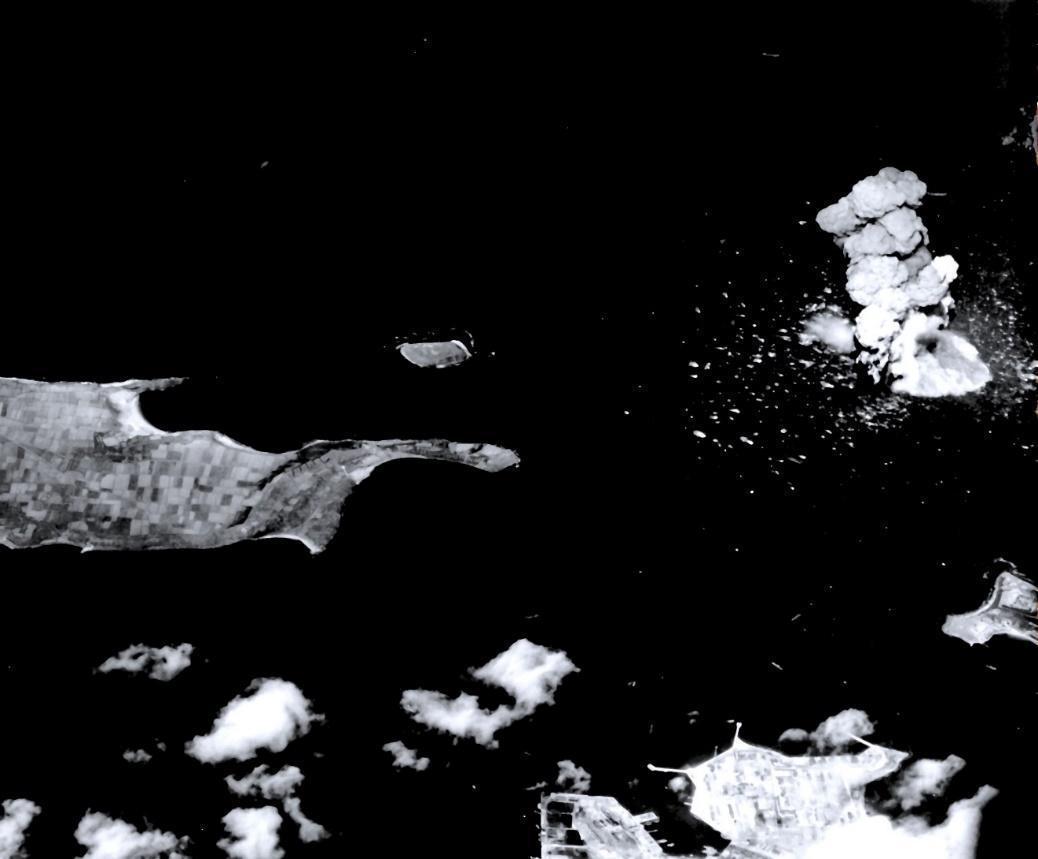 1944/10/12,美軍艦載機空襲澎湖。本圖左方中景為風櫃半島,前方近景為測天島海軍基地,右方中景為金龍頭。馬公港入口處的海域有船艦被命中,煙柱直竄天際。