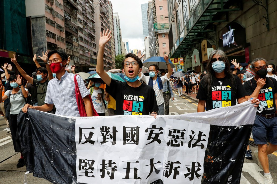 「七一遊行」今年遭禁,民眾仍自發上街。圖左至右為朱凱廸、陳皓桓、梁國雄。 圖/路透社