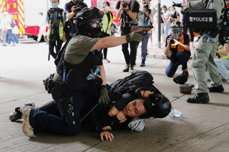 香港警方一面壓制反對港版國安法的示威者,一面舉起胡椒噴劑槍瞄向其他示威群眾。(路透)