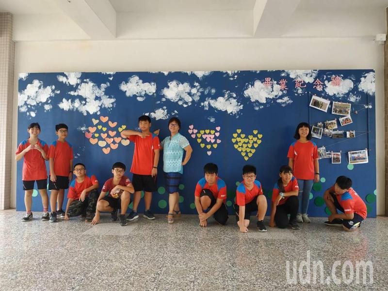 雲林麥寮興華國小校長王瓊慈(中間藍衣者)與畢業生們在校園網美牆合影留念。記者陳苡葳/攝影